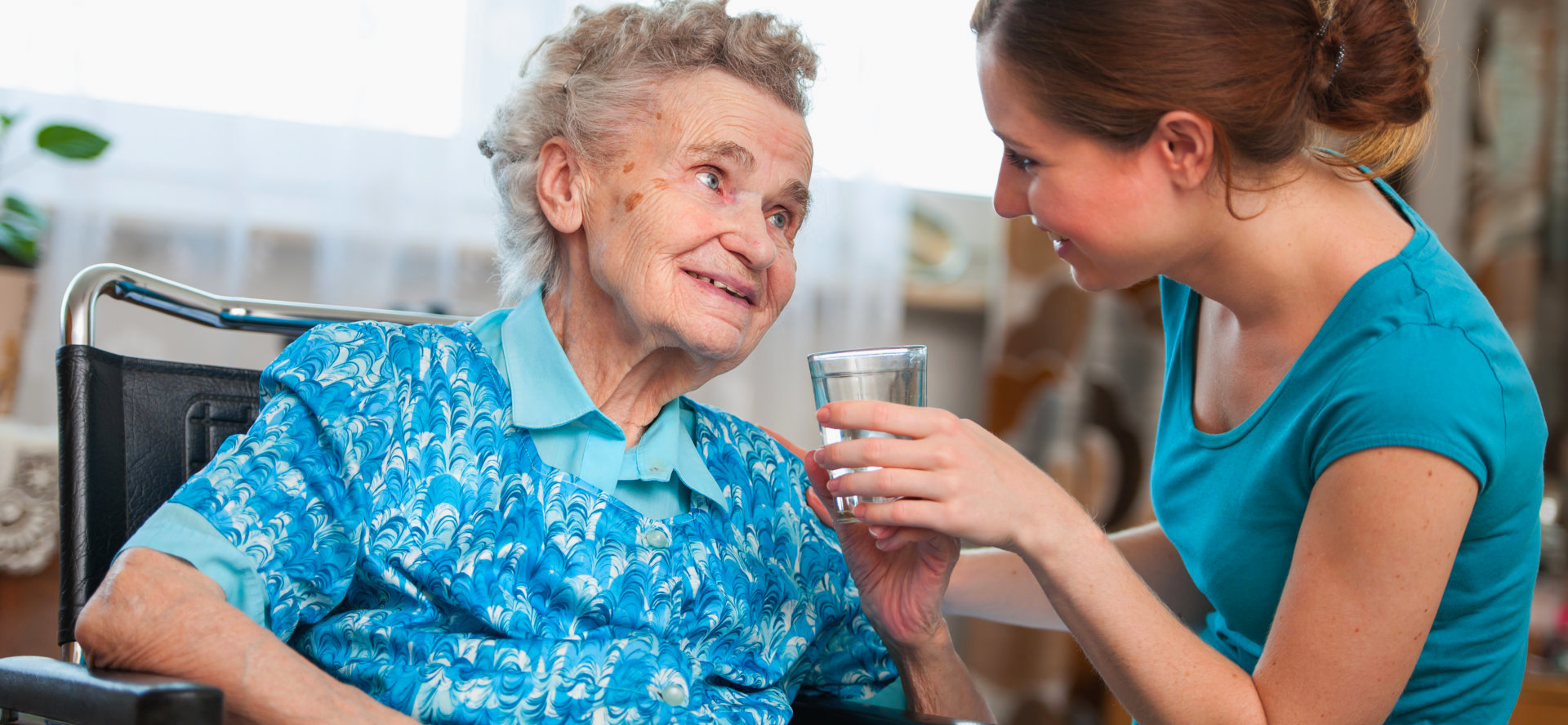 caregiver serving water to an old woman