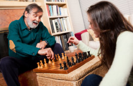 caregiver and old man playing chess