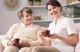 caregiver and old woman drinking coffee